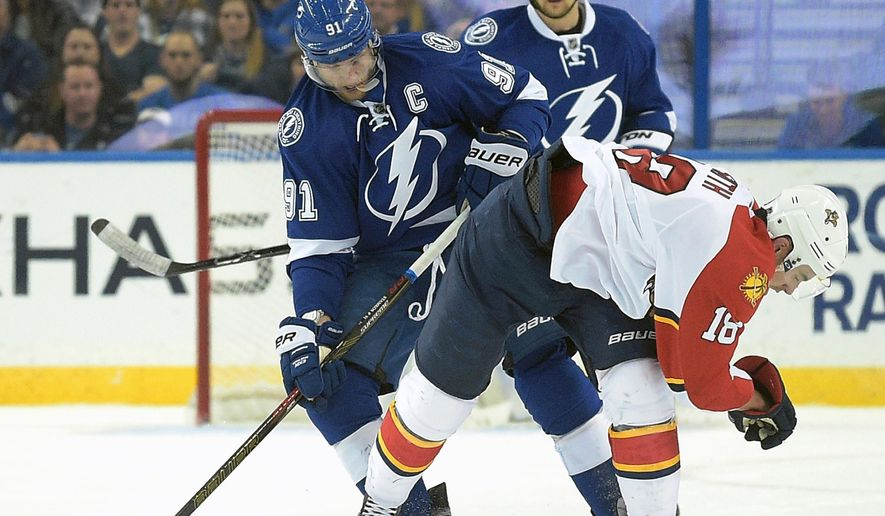 Tampa Bay Lightning center Steven Stamkos (91) takes the puck away from Florida Panthers right wing Reilly Smith (18) during the second period of an NHL hockey game in Tampa, Fla., Sunday, Jan. 17, 2016. (AP Photo/Phelan M. Ebenhack)