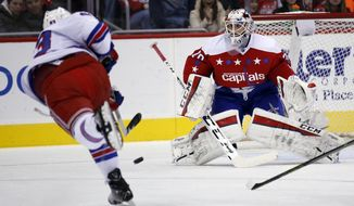 New York Rangers defenseman Keith Yandle (93) shoots as Washington Capitals goalie Braden Holtby (70) waits to block the shot, in the first period of an NHL hockey game, Sunday, Jan. 17, 2016, in Washington. (AP Photo/Alex Brandon)
