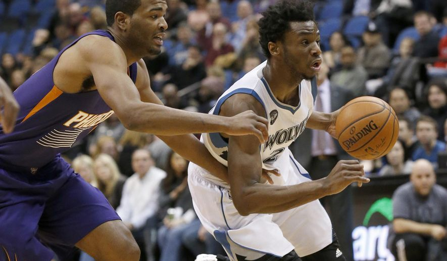 Minnesota Timberwolves guard Andrew Wiggins, right, drives past Phoenix Suns forward T.J. Warren, left, during the first half of an NBA basketball game in Minneapolis, Sunday, Jan. 17, 2016.  (AP Photo/Ann Heisenfelt)