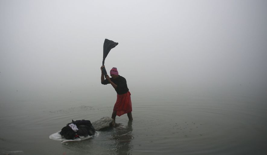 An Indian washerman works on the banks of the River Brahmaputra on a foggy winter morning in Gauhati, India, Monday, Jan. 18, 2016. (AP Photo/Anupam Nath)
