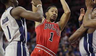 Chicago Bulls guard Derrick Rose (1) passes around the defense of Detroit Pistons guard Reggie Jackson (1) during the first half of an NBA basketball game, Monday, Jan. 18, 2016 in Auburn Hills, Mich. (AP Photo/Carlos Osorio)