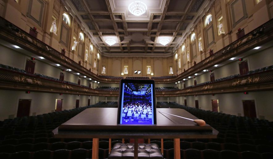 In this Friday, Jan. 15, 2016, photo, an iPad with a Boston Symphony Orchestra interactive program is displayed on the conductor's stand at Symphony Hall in Boston. The BSO is loaning iPads to concertgoers during performances in hopes of drawing new audiences to classical music. (AP Photo/Charles Krupa)
