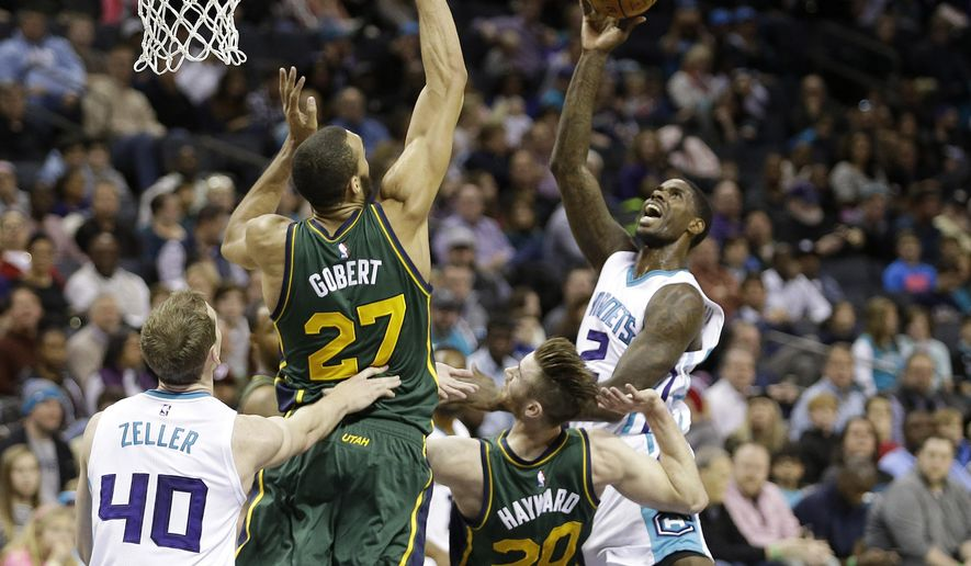 Charlotte Hornets' Marvin Williams (2) tries to guide his shot over the outstretched arm of Utah Jazz's Rudy Gobert (27) as the Charlotte Hornets' Cody Zeller (40) and the Utah Jazz's Gordon Hayward (20) look on during the first half of an NBA basketball game Monday, Jan. 18, 2016,  in Charlotte, N.C. (AP Photo/Bob Leverone)