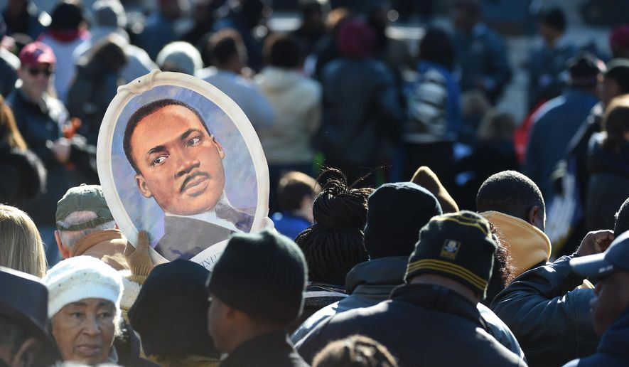 Attendees hold a portrait of Martin Luther King Jr. during the King Day at the Dome event, Monday, Jan. 18, 2016, in Columbia, S.C. (AP Photo/Rainier Ehrhardt)