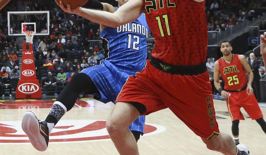 Atlanta Hawks center Tiago Splitter (11) goes to the basket against Orlando Magic forward Tobias Harris (12) in the first  NBA basketball game, Monday, Jan. 18, 2016, in Atlanta. (AP Photo/John Bazemore)