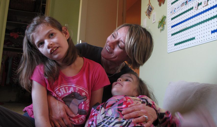 FILE - In this Feb. 27, 2015 file photo, Alexis Carey, left, sits with her mother Clare Carey, center, and her sister Alanis Carey, right, in Boise, Idaho. Alexis has a rare form of epilepsy, however, her family is hoping the Idaho Legislature will decriminalize marijuana extract oil to help reduce her seizures. Idaho health officials say children with severe forms of epilepsy are benefiting from a program that allows parents to access an experimental drug derived from marijuana. An April executive order from Idaho Gov. Butch Otter is allowing the very limited use of the non-psychoactive drug.  (AP Photo/Kimberlee Kruesi, File)