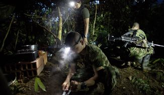 In this Jan. 3, 2016 photo, with the aid of head lamps, rebel fighters for the 36th Front of the Revolutionary Armed Forces of Colombia or FARC, prepare a breakfast of rice, beans, sausages and coffee, in their hidden camp in Antioquia state, in the northwest Andes of Colombia. The day begins around 4:30 a.m. inside the temporary camp, home to 22 rank and file fighters, 4 commanders and 2 dogs. All rank and file are expected to share in kitchen patrol. (AP Photo/Rodrigo Abd)