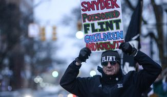 Mike Ahrens of Muskegon, Mich., poses for photo with his sign about Flint's water crisis Monday, Jan. 18, 2016, in Ann Arbor, Mich. Michigan Gov. Rick Snyder responded Monday to criticism from presidential candidate Hillary Clinton during the Democratic debates for his handling of Flint's water emergency, saying Clinton is making it a political issue. (Junfu Han/The Ann Arbor News via AP) LOCAL TELEVISION OUT; LOCAL INTERNET OUT; MANDATORY CREDIT