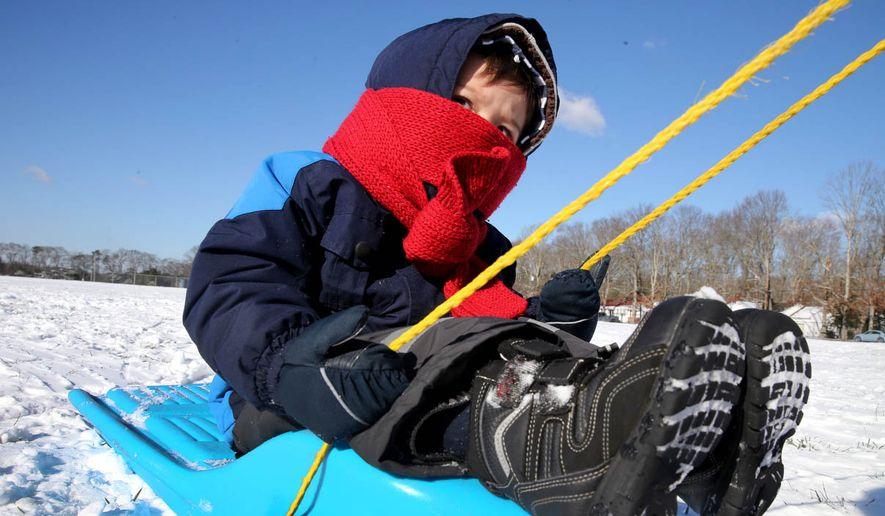 Stefan Markovic  2, is bundled up against the cold while sledding at Mainland Regional High School in Linwood, N.J., Monday, Jan. 18, 2016. (Vernon Ogrodnek/The Press of Atlantic City via AP) MANDATORY CREDIT
