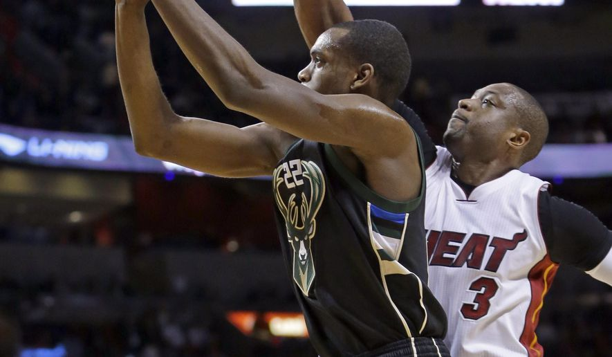 Milwaukee Bucks guard Khris Middleton (22) goes to the basket as Miami Heat guard Dwyane Wade (3) defends during the first half of an NBA basketball game, Tuesday, Jan. 19, 2016, in Miami. (AP Photo/Alan Diaz)