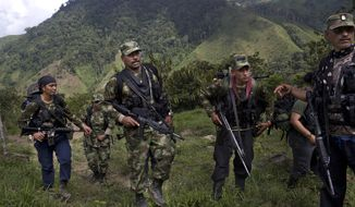 In this Jan. 6, 2016 photo, Juan Pablo, center, a commander of the 36th Front of the Revolutionary Armed Forces of Colombia, or FARC, walks with his comrades in Antioquia state, in the northwest Andes of Colombia. As a commander of the 36th Front, one of the most militarily-active in a half century of warfare, the 41-year-old is capable of reciting verbatim passages from Fidel Castro's speeches even though he's never been to the movies, driven a car or eaten in a restaurant. (AP Photo/Rodrigo Abd)