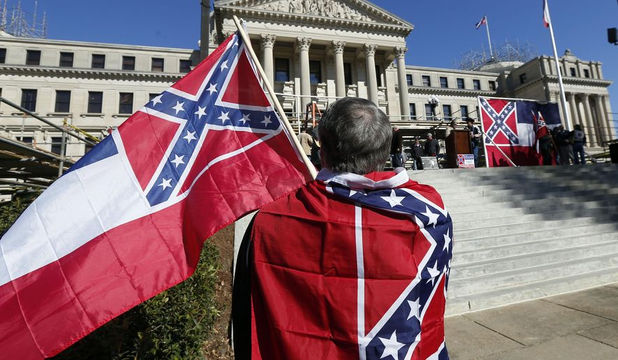 Sons of Confederate Veterans and other groups parade on the grounds of the state Capitol in Jackson, Miss., Tuesday, Jan. 19, 2016, in support of keeping the Confederate battle emblem on the state flag. The public display of Confederate symbols has come under increased scrutiny since June, when nine black worshippers were massacred at a church in South Carolina.  (AP Photo/Rogelio V. Solis)