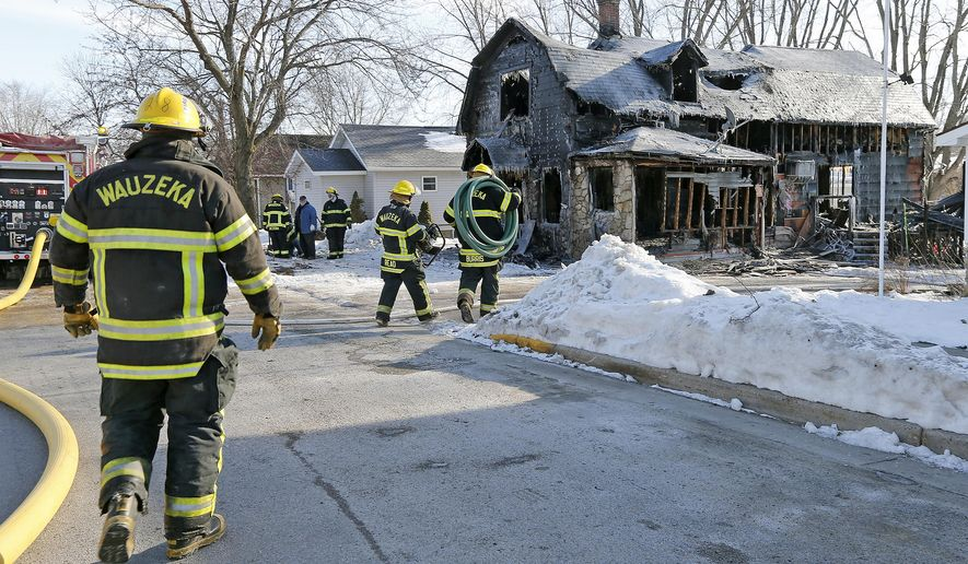 Members of the Wauzeka, Wis. fire department work the aftermath of a house fire that took the lives of two people, Tuesday, Jan. 19, 2015 in Wauzeka, Wis. Two girls have died in a house fire in Crawford County.Sheriff's officials say the victims are ages 12 and 15. Firefighters were called to a house in the Village of Wauzeka about 11:30 p.m. Monday. (Dave Kettering/Telegraph Herald via AP) MANDATORY CREDIT