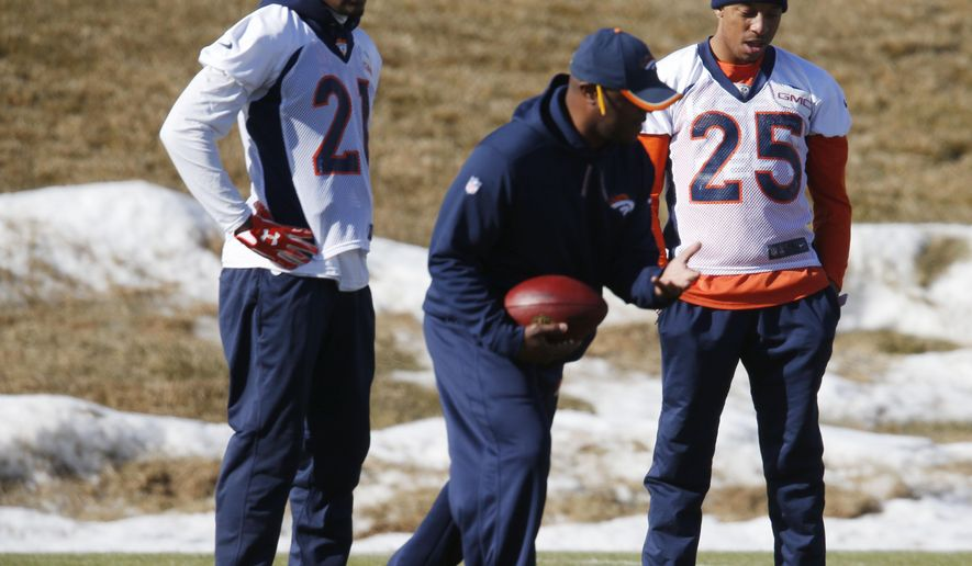 Denver Broncos cornerback Aqib Talib, left, and Denver Broncos cornerback Chris Harris, right, listen to a coach during an NFL football practice Wednesday, Jan. 20, 2016, at the team's headquarters in Englewood, Colo. The Broncos will host the New England Patriots in the AFC Championship Sunday in Denver. (AP Photo/David Zalubowski)