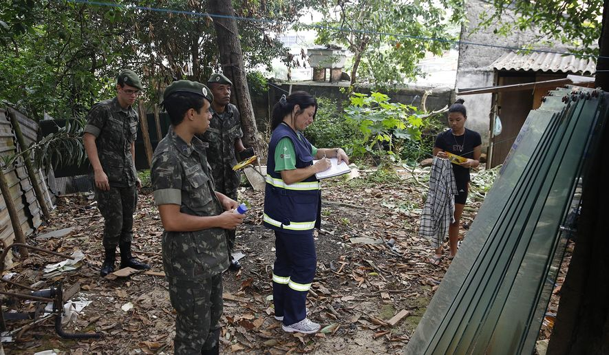 Army soldiers and a health agent from Sao Paulo's Public health secretary check a residence during an operation against the Aedes aegypti mosquito, which is a vector for transmitting the Zika virus in Sao Paulo, Brazil, Wednesday, Jan. 20, 2016. (AP Photo/Andre Penner)