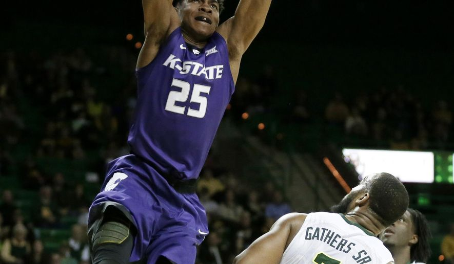 Kansas State forward Wesley Iwundu (25) dunks the ball over Baylor's Rico Gathers (2) as Taurean Prince, rear, watches in the first half of an NCAA college basketball game, Wednesday, Jan. 20, 2016, in Waco, Texas. (AP Photo/Tony Gutierrez)