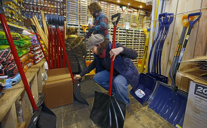 Patty O'Brien, center, kneels down in the back of Rittenhouse Hardware to compare the snow shovels that are for sale in Pennsylvania on Thursday, Jan. 21, 2016. She was looking for one to just dig her car out of a parking space. Much of southern Pennsylvania is expected to receive a foot or more of snow from an approaching winter storm as plowing crews and state troopers prepare to work overtime to clear highways and respond to emergencies. (Michael Bryant/The Philadelphia Inquirer via AP) MANDATORY CREDIT