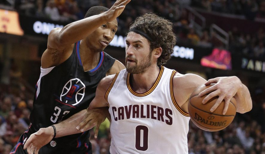 Cleveland Cavaliers' Kevin Love, right, drives to the basket against Los Angeles Clippers' Wesley Johnson in the first half of an NBA basketball game Thursday, Jan. 21, 2016, in Cleveland. (AP Photo/Tony Dejak)