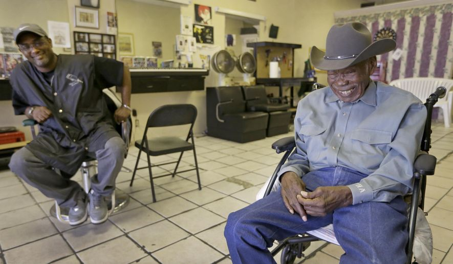 ADVANCE FOR USE SUNDAY, JAN. 24 - In this photo taken Friday, Jan. 8, 2016, Paul Cleveland, 81, a member of the National Cowboys of Color Hall of Fame, shares a laugh with barber Charles Jones at Mr. C's Barber Shop in Humble, Texas. Considered a trailblazer for the African-American cowboy, Cleveland was part of the Houston Livestock Show and Rodeo's 1966 debut in what was billed as the world's first domed stadium.  (Melissa Phillip/Houston Chronicle via AP) MANDATORY CREDIT