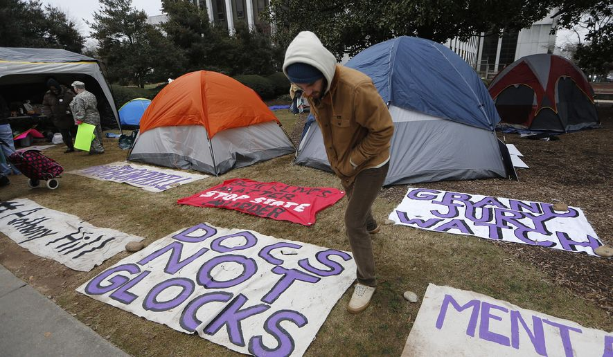 A man looks at signage in a camp outside the Dekalb County Courthouse in Decatur, Ga., Thursday, Jan., 21, 2016, as people await the decision by a grand jury considering whether a police officer is to be indicted after the shooting death of an unarmed naked man. DeKalb County District Attorney Robert James announced earlier this month he would seek an indictment against Officer Robert Olsen. (AP Photo/John Bazemore)