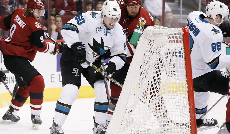 San Jose Sharks' Chris Tierney (50) stuffs the puck in for a goal as Arizona Coyotes' Nicklas Grossmann (2), of Sweden, and Viktor Tikhonov (9), of Russia, defend and Sharks' Melker Karlsson (68), of Sweden, falls into the goal during the first period of an NHL hockey game, Thursday, Jan. 21, 2016, in Glendale, Ariz. (AP Photo/Ross D. Franklin)