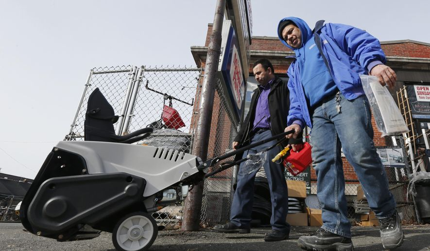 Mario Argueta, left, of Hackensack, N.J., and friend Alex Sorto leave Meadowlands Hardware after purchasing a snow blower ahead of the weekend's snowstorm, Friday, Jan. 22, 2016, in Rutherford, N.J. Towns across the state are hunkering down in preparation for a major snowstorm expected to begin later in the day. (AP Photo/Julio Cortez)