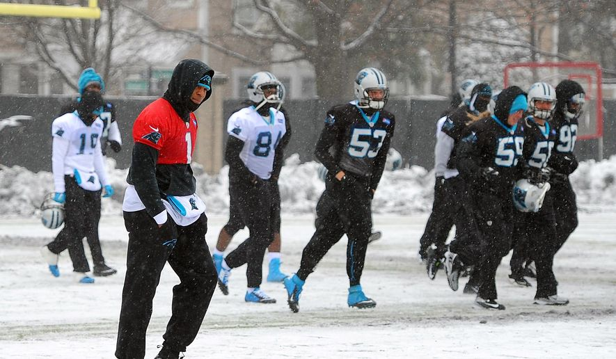 Carolina Panthers quarterback Cam Newton, left, walks across a practice field covered in snow and ice, Friday, Jan. 22, 2016, in Charlotte, N.C. The Panthers host the Arizona Cardinals in the NFC championship NFL football game on Sunday. (Jeff Siner/The Charlotte Observer via AP) MAGS OUT; TV OUT; MANDATORY CREDIT