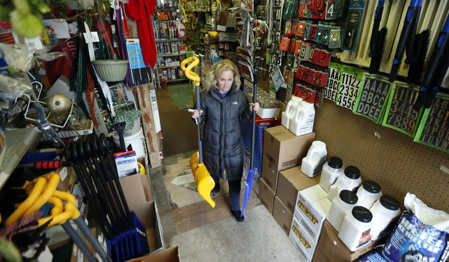 Donna Przychodzki, of Secaucus, N.J., leaves Meadowlands Hardware with two snow shovels purchased in preparation for the weekend's storm, Friday, Jan. 22, 2016, in Rutherford, N.J. Towns across the state are hunkering down in preparation for a major snowstorm expected to begin later in the day. (AP Photo/Julio Cortez)