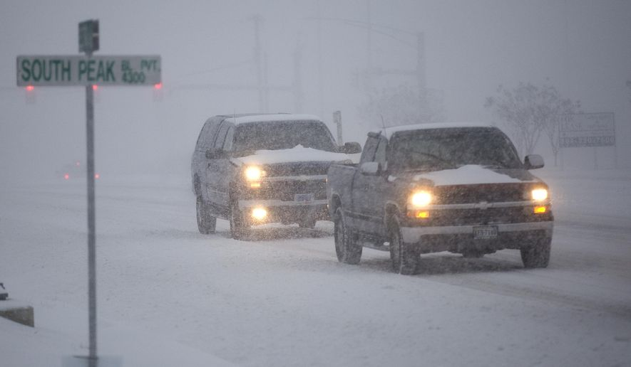 Cars drive in the snow along Electric Road in southwest Roanoke County on Friday morning, Jan. 22, 2016, near Roanoke, Va. A blizzard menacing the Eastern United States started dumping snow in Virginia, Tennessee and other parts of the South on Friday as millions of people in the storm's path prepared for icy roads, possible power outages and other treacherous conditions.  (Erica Yoon/The Roanoke Times via AP)