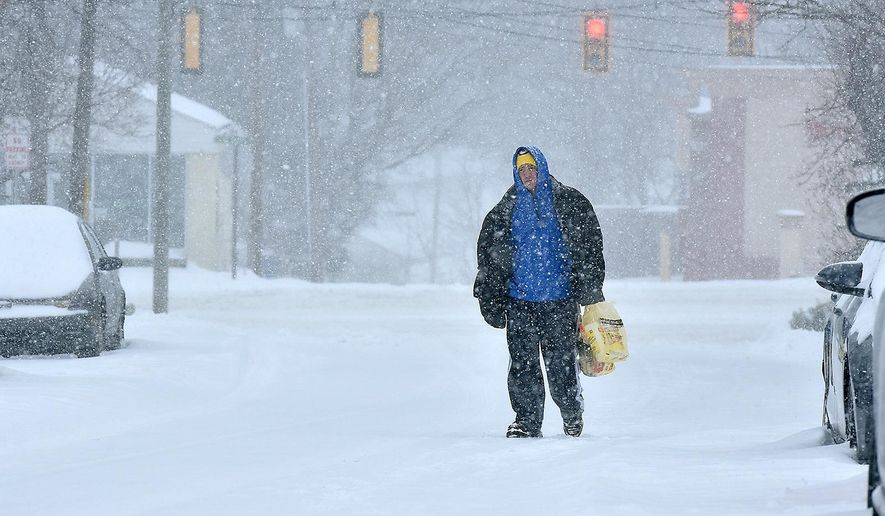 Darren Dunford, on his way home from story, trudges along 4th Street as snow falls Friday, Jan. 22, 2016, in Beckley, W.Va.  A blizzard menacing the Eastern United States started dumping snow in Virginia, Tennessee and other parts of the South on Friday as millions of people in the storm's path prepared for icy roads, possible power outages and other treacherous conditions. (Brad Davis/The Register-Herald via AP) MANDATORY CREDIT