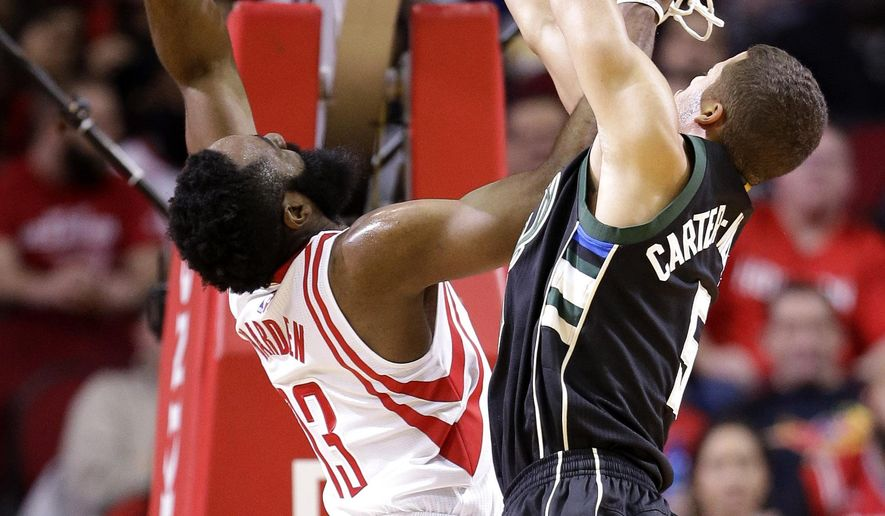Houston Rockets' James Harden (13) goes up to shoot as Milwaukee Bucks' Michael Carter-Williams (5) defends during the first half of an NBA basketball game Friday, Jan. 22, 2016, in Houston. (AP Photo/David J. Phillip)