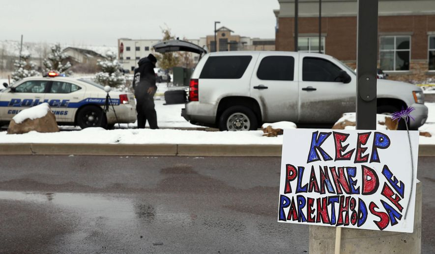 FILE - In this Nov. 29, 2015 file photo, a sign in support of Planned Parenthood stands just south of the clinic as police investigators gather evidence near the scene of a shooting at the clinic in Colorado Springs, Colo. Abortion and reproductive rights are never far from the nerve in this battleground state, where party affiliation is roughly even between Democrats and Republicans and statewide contests often come down to the votes of suburban women who belong to neither party.(AP Photo/David Zalubowski, File)