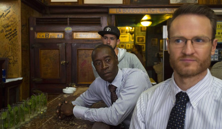 "In this Jan. 15, 2016 photo, ""House of Lies"" actors Don Cheadle and Josh Lawson, right, sit at the bar counter in Bodeguita Del Medio during the filming of an episode, in Havana, Cuba. The producers of Showtime's dark comedy ""House of Lies"" had $3 million and a mission: shoot the first episode of scripted American television in Cuba in more than half a century. (AP Photo/Desmond Boylan)"