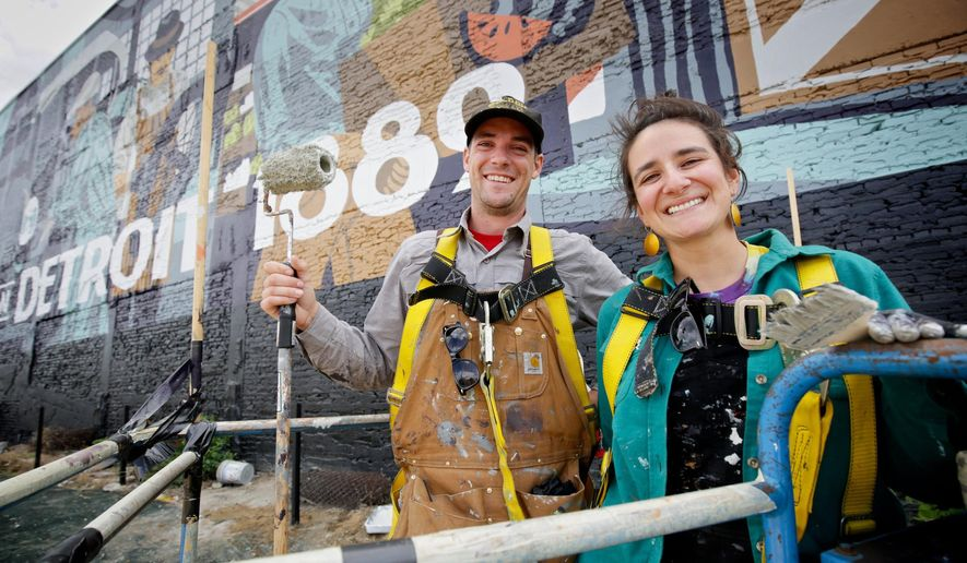 ADVANCE FOR MONDAY, JAN. 25, 2016 AND THEREAFTER - In this photo taken on Monday, Aug. 24, 2015, Kelly Golden, right, and Jordan Zielke, both of New Baltimore, Mich., pose during their break as they work on a new mural on the wall of the new Carhartt store in Detroit.  The duo is creating hand-painted signs for many of Detroit's new storefronts and beyond.  The mural was illustrated by James Noellert and Michael Eugene Burdick.  (Salwan Georges /Detroit Free Press via AP)  DETROIT NEWS OUT; TV OUT; MAGS OUT; NO SALES; MANDATORY CREDIT DETROIT FREE PRESS