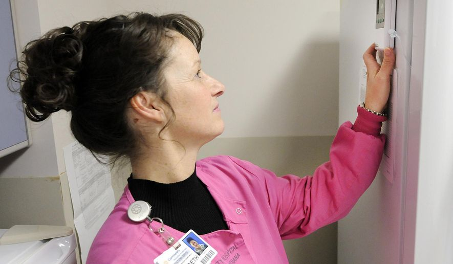 In this photo taken on Wednesday, Jan. 13, 2016, Community Hospital's Lactations Services coordinator Elizabeth Arnett checks the temperature of a freezer used to store donated breast milk at Community Hospital in Anderson Ind. Donated mother's milk is sent off to be screened and pasteurized. (Don Knight/The Herald-Bulletin via AP) MANDATORY CREDIT