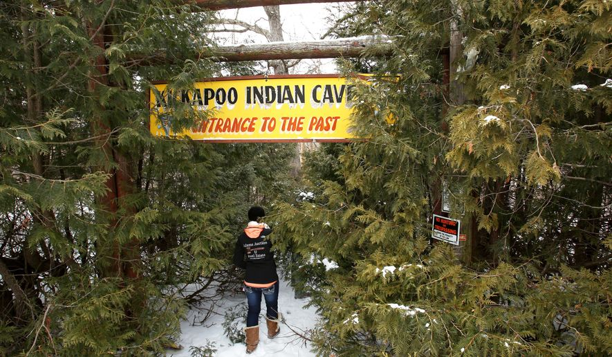 ADVANCE FOR USE MONDAY, JAN. 25 - In this photo taken Wednesday, Jan. 13, 2016, Megan Mahan, with Adams Auction and Real Estate in Prairie du Chien, enters the overgrown trail that leads to the gift shop, museum and entrance of Kickapoo Indian Caverns near Wauzeka, Wis. The owner, Delores Gaidowski, died in 2014 and her family put the property up for sale in September. The initial asking price was $700,000, but it was recently reduced to $499,000.  (Amber Arnold/Wisconsin State Journal via AP) MANDATORY CREDIT