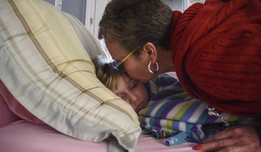 ADVANCE FOR SUNDAY, JAN. 24, 2016 AND THEREAFTER - In this photo taken on Thursday, Dec. 17, 2015, Terrie Morrow kisses her sleeping daughter Abigail, 10, on the forehead to say goodnight at their home in Holland, Mich. Empty nesters, Terrie Morrow and her husband Cal officially adopted Abigail in October. Abigail has been in roughly six foster homes and has had over 22 parent figures in her lifetime.  (Taylor Ballek /The Grand Rapids Press via AP) ALL LOCAL TELEVISION OUT; LOCAL TELEVISION INTERNET OUT; MANDATORY CREDIT