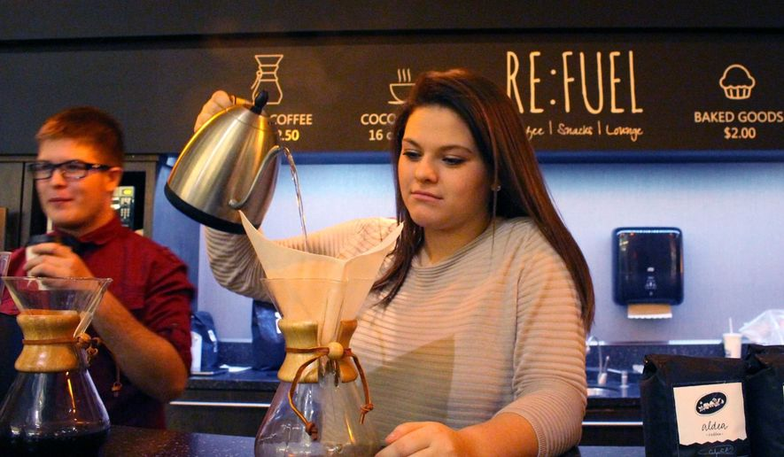 In a photo taken Jan. 14, 2016, Sierra Hauch, 16, a sophomore at iCademy Global, pours hot water over coffee grounds at Re:fuel, a new student-run and operated coffee shop at the school building in Zeeland, Mich. Re:Fuel, a student-designed and operated coffee shop at a Zeeland charter school, is now open for business. Students at the school have been creating a business plan for the shop for at least the past year. In May 2015, a group of high school students traveled to Honduras to learn more about the economy of coffee _ and how important it is to the local growers that they be paid fairly for their hard work. (Amy Biolchini/The Holland Sentinel via AP)