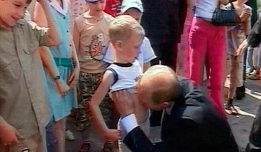 Russian President Vladimir Putin lifts the shirt of a young boy named Nikita and kisses his stomach June 28 at the Kremlin in Moscow, in this image taken from Russian state television. (Associated Press, file)