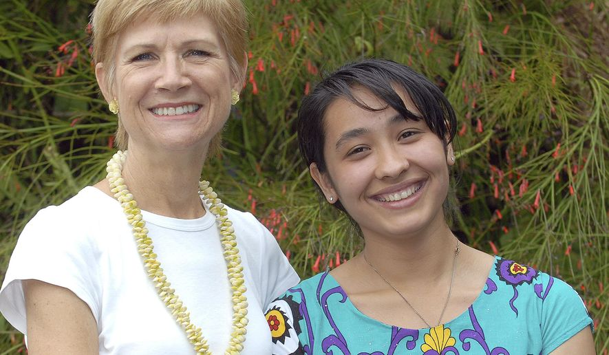 ADVANCE FOR WEEKEND JAN. 23-24, 2016 AND THEREAFTER -  In this Jan. 15, 2016 photo host mother Pamela Wang, left, poses with exchange student Mehrangez Rahmatova in Kealakekua, Hawaii.  Rahmatova, 19, was on the Big Island in 2012 as a student at Konawaena High School. Living in the United States has been a major shift from the post-Soviet, largely mono-cultural, and patriarchal culture of her homeland, Tajikistan. (Laura Shimabuku/West Hawaii Today via AP)