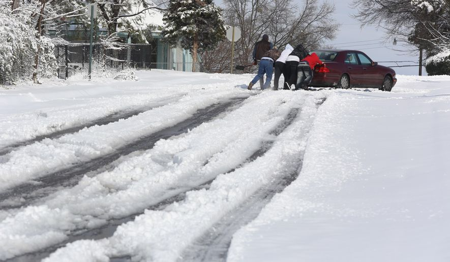A group of men help push a car through the snow up hill onto 11th Street Friday, Jan. 22, 2016, in Little Rock, Ark. Heavy snow fell overnight with Little Rock and North Little Rock accumulating 4-6 inches of snow in some parts. (Melissa Sue Gerrits/The Arkansas Democrat-Gazette via AP)  ARKANSAS TIMES OUT; ARKANSAS BUSINESS OUT; MANDATORY CREDIT