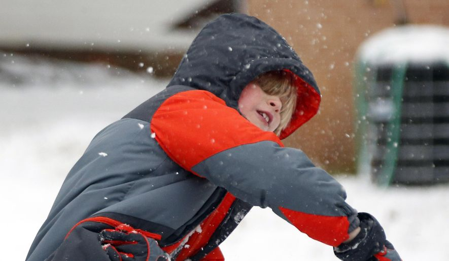 """Max Hill, 8, tosses his """"perfect"""" snowball in a neighborhood snowball fight, Friday, Jan. 22, 2016, in Oxford, Miss. Early morning snow provided plenty of fun for the children as school officials had earlier called for closure of the public schools. (AP Photo/Rogelio V. Solis)"""