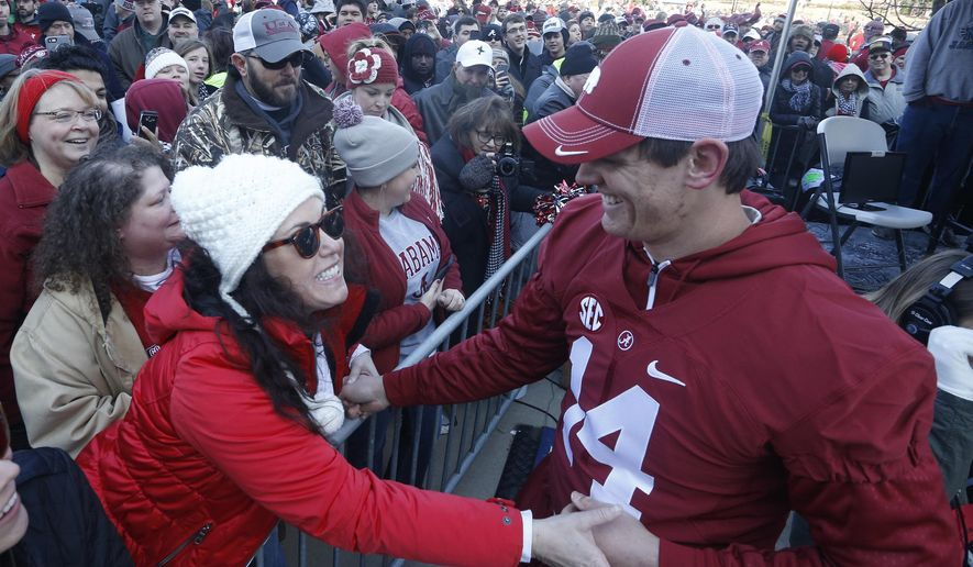 Fan Cindi Bradley, from Huntsville, urges Alabama quarterback Jake Coker to pose for a picture, Saturday, Jan. 23, 2016, in Tuscaloosa, Ala. Alabama football fans turned out by the thousands to celebrate the Crimson Tide's 4th National Championship in seven years. (AP Photo/Hal Yeager)