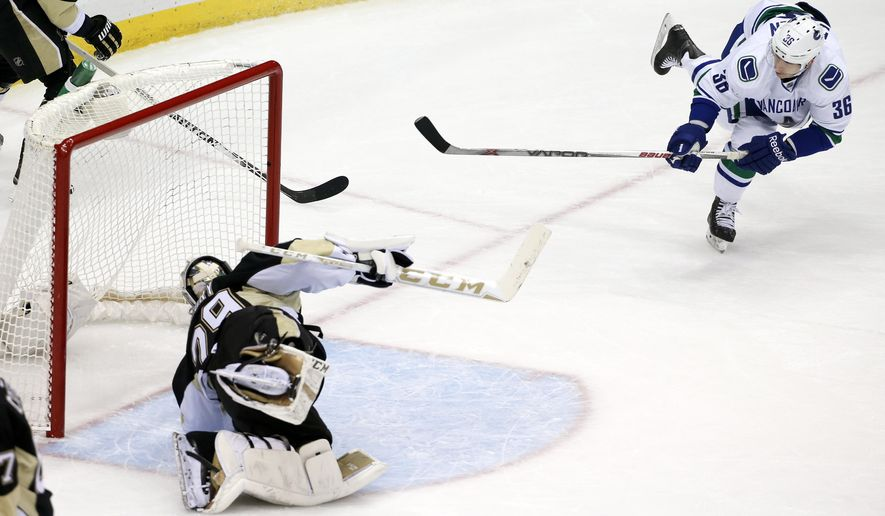 Vancouver Canucks' Jannik Hansen (36)  backhands a rebound past Pittsburgh Penguins goalie Marc-Andre Fleury (29) for his second goal of the first period of an NHL hockey game in Pittsburgh, Saturday, Jan. 23, 2016. (AP Photo/Gene J. Puskar)