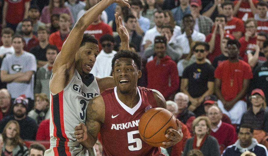 Arkansas guard Anthlon Bell (5) drives past Georgia guard J.J. Frazier (30) during an NCAA college basketball game Saturday, Jan. 23, 2016, in Athens, Ga. (Taylor Craig Sutton/Athens Banner-Herald via AP)