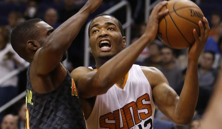 Phoenix Suns forward T.J. Warren (12) drives on Atlanta Hawks guard Tim Hardaway Jr. in the second quarter during an NBA basketball game, Saturday, Jan. 23, 2016, in Phoenix. (AP Photo/Rick Scuteri)