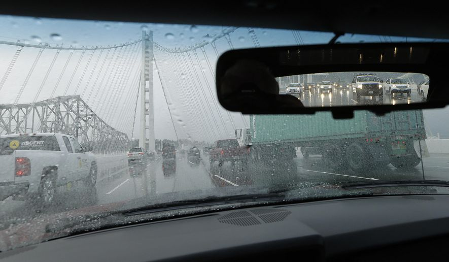 FILE - In this Feb. 28, 2014 file photo, traffic is seen traversing the eastern span of the San Francisco-Oakland Bay Bridge during a rainstorm in San Francisco. Caltrans has found a simple and cheap solution to eliminate leaks in the Bay Bridge's new eastern span that could cause corrosion and other damage to the cable at its anchorages, authorities announced Friday, Jan. 22, 2016. Bridge officials said almost no water is making it into the hollow steel structures despite recent heavy rains thanks to industrial-grade caulk used to seal the gaps between the asphalt road surface and the guardrails, the San Francisco Chronicle reported. (AP Photo/Ben Margot, File)
