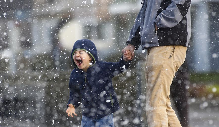 Christophe Pouchard and his son, Lucas, 4, of San Francisco, are sprayed with water as huge waves crash over the seawall on Beach Boulevard in Pacifica, Calif., on Saturday, Jan. 23, 2016. The city of Pacifica has declared a local emergency due to El Nino storm damage. (John Green/Bay Area News Group via AP)