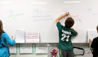 In this Monday, Dec. 14, 2015, file photo, second-graders write out their math solutions at Sageville Elementary School in Sageville, Iowa. Common Core standards for mathematics expect students to conceptually understand math. Multiple strategies, versus a single algorithm, are taught. Forty-two states, including Iowa, Wisconsin and Illinois, have adopted the standards designed to prepare K-12 students for higher education and the professional world. (Jessica Reilly/Telegraph Herald via AP) ** FILE **