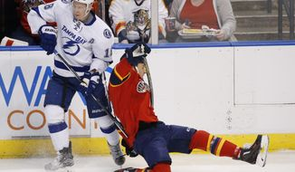 Tampa Bay Lightning left wing Ondrej Palat (18) and Florida Panthers center Derek MacKenzie (17) battle for the puck during the first period of an NHL hockey game, Saturday, Jan. 23, 2016 in Sunrise, Fla. (AP Photo/Wilfredo Lee)